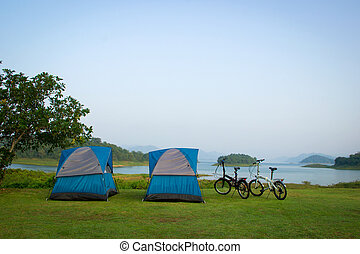 Blue camping tents and 2 bicycle on a shore in a morning - 2...