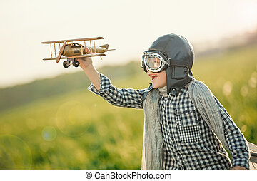 Aviator - Little boy with wooden airplane in the field