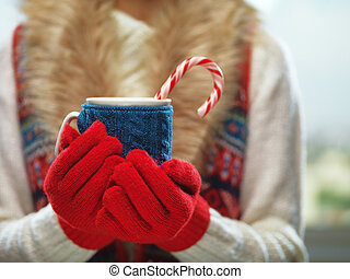 Woman hands in woolen red gloves holding a cozy mug with hot...