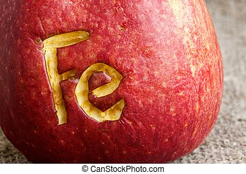 Abbreviation Fe scratched on an apple skin Close up