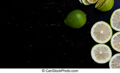 Green lemon slices on a black wooden surface. Background....