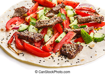 Beef shawarma wrap with vegetables. Close up, selective...