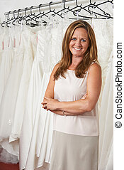 Portrait Of Female Bridal Store Owner With Wedding Dresses