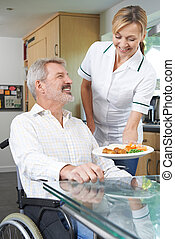 Carer Serving Meal To Man In Wheelchair At Home