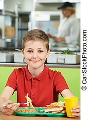 Male Pupil Sitting At Table In School Cafeteria Eating...