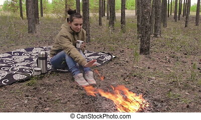 Girl in the forest near a campfire