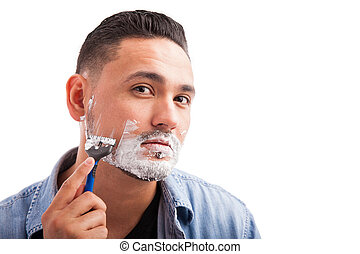 Hispanic young man shaving his beard - Young Hispanic man...