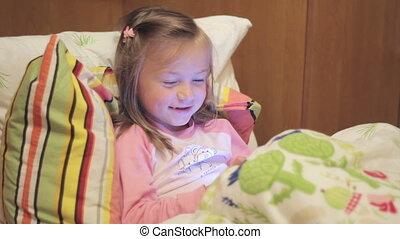 little girl with the tablet on the bed singing a song
