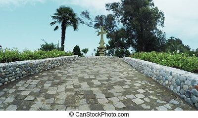 Stone cross surrounded by palm trees - In botanical park...