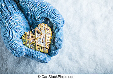 Female hands in teal knitted mittens with a entwined vintage...