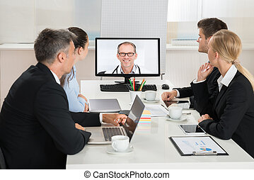 Businesspeople Videoconferencing With Doctors - Team Of...