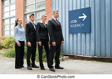 Businesspeople Waiting In A Row Near The Job Agency...