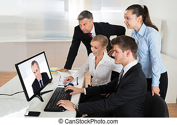 Businesspeople Videoconferencing On Computer -...