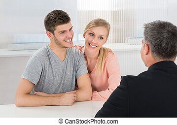 Couple Talking With Male Agent - Young Happy Couple Talking...