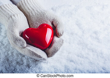 Female hands in white knitted mittens with a glossy red...