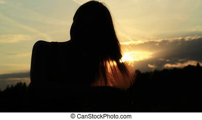 A silhouette of a woman  on a sunset comb her hair