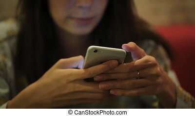 dark-haired girl sitting with a phone in a cafe, watching...