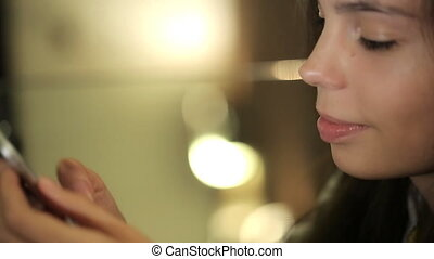 Point of view of a young woman using a smart phone for texting and browsing content. Focus on the woman face