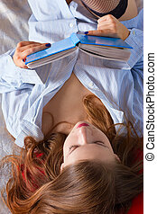 Beautiful young  woman reading book on the bed at home