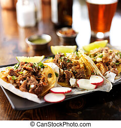 three authentic mexican street tacos with barbacoa, carnitas...