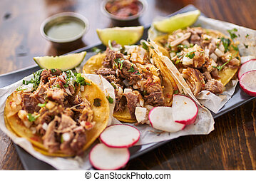 three street tacos in yellow corn tortilla with different...