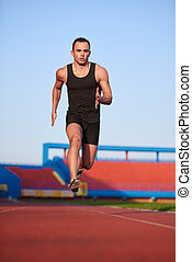 Athletic man start - Sprinter leaving starting blocks on the...