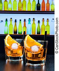 two glasses of spritz aperitif aperol cocktail with orange slices and ice cubes on bar table, disco atmosphere background