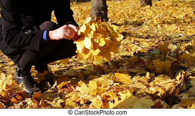Happy girl in autumn park throws yellow fallen leaves -...