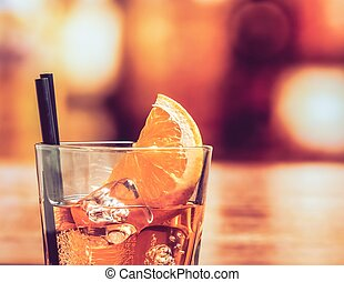 detail of glass of spritz aperitif aperol cocktail with orange slices and ice cubes on bar table, vintage atmosphere background