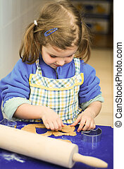 Gingerbread baking - Cute little girl rolling dough for...