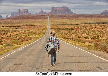 Wanderer or loner in Monument Valley walking down an empty...