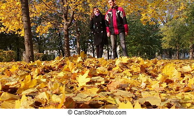 Young man and girl walking in the autumn park holding hands.