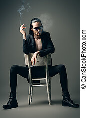 cigarette - Grunge man in black suit and sunglasses smoking...