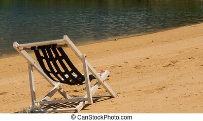 closeup white wooden beach chair stands on golden sand by...