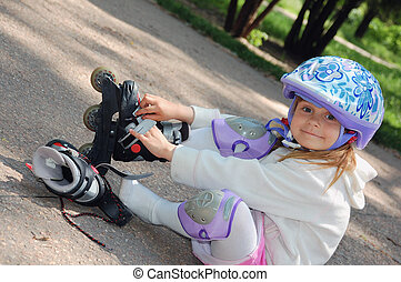 rollerblading - Four year old child putting on her in-line...