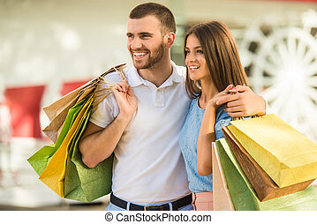 Loving couple on a date - Loving young couple with bags for...