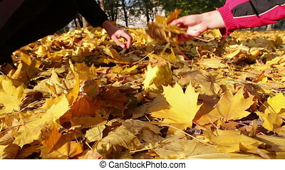 A girl and a man throw the yellow fallen leaves in the...