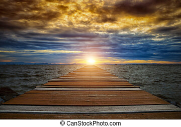 Wooden walkway into the lake with sunset.