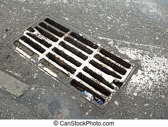 Drain grate on the road with old white road marking line...