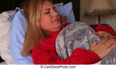 Sick woman lying on a bed and having abdominal pain