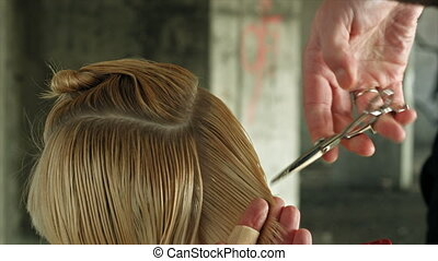 Young fashion woman hairdresser makes hairstyle for a girl....