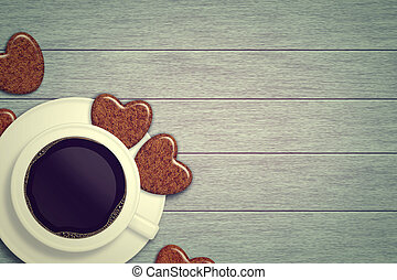 mug of coffee with heart cookies lying on wooden table with...