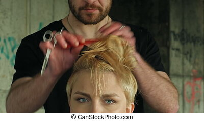 The master does a hairdress to a blond girl.