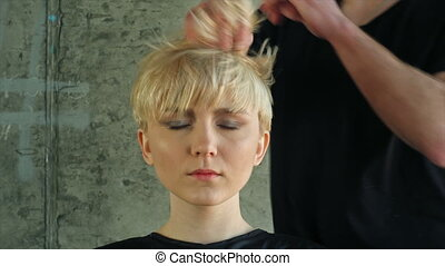 Closeup on young woman getting new hairdress by hairdresser.