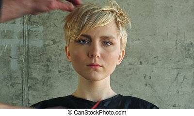 Final touch by hairdresser. Blond girl hairdress.