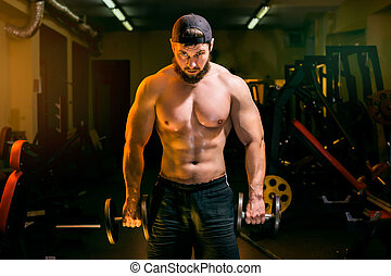 man in gym training with dumbbells