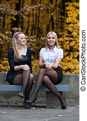 two young girls talking in the autumn park