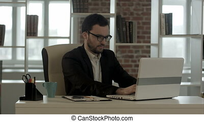 Businessman typing on his keyboard funny glasses