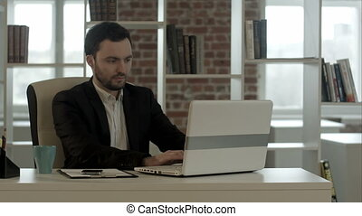 Businessmanworking on his computer in office while typing on...