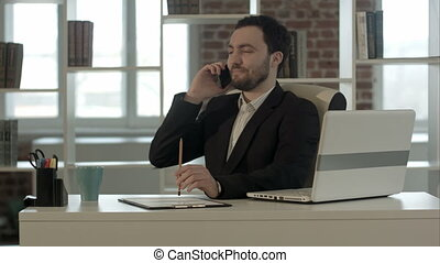 Happy smiling young man talking on mobile phone in office